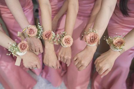 Close-up van handen bruidsmeisje met bloem en roze jurk