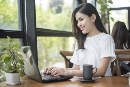 Beautiful business girl working with tablet , smartphone and drinking coffee in coffee shop
