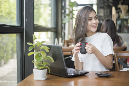 Beautiful business girl working with tablet , smartphone and drinking coffee in coffee shop Stock Photo