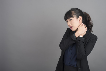 Business Woman Neck pain on grey background Stock Photo