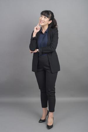 Beautiful Business Woman thinking on grey background