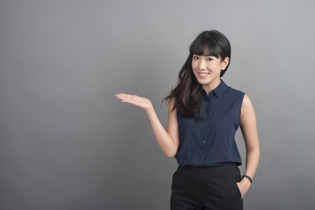 Beautiful Business Woman presenting something on grey background