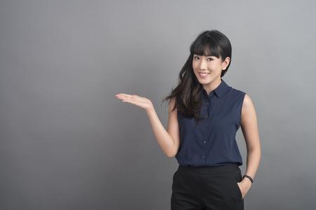 Mooie bedrijfsvrouw die iets op grijze achtergrond voorstellen Stockfoto