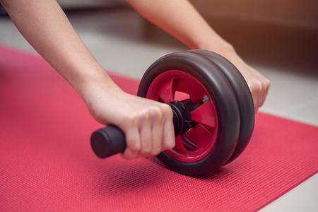 roller: close up sporty woman  do abdominal exercises with wheel at home