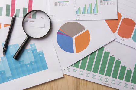 Lupe und Dokumente mit Analytics Daten auf Holztisch liegen Standard-Bild - 82889908
