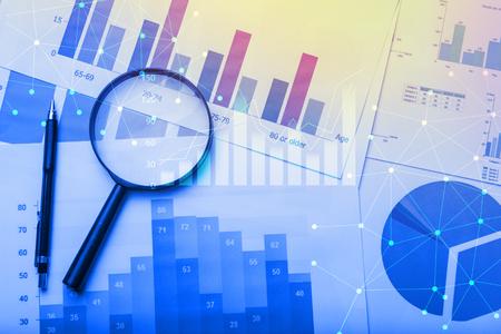 Lupe und Dokumente mit Analytics-Daten auf dem Tisch liegend, selektiven Fokus