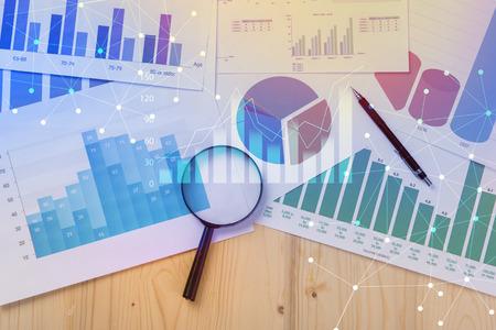 Lente di ingrandimento e documenti con dati di analisi che si trovano sul tavolo, fuoco