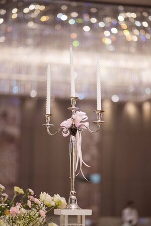 White wedding flowers background candle with bokeh in wedding hall