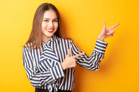 Beautiful business woman is presenting something on yellow background