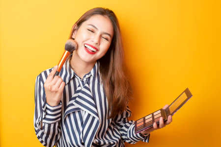 Beautiful makeup artist woman is happy on yellow background