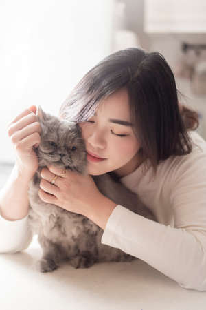 Beautiful asian cat lover woman is playing with cat in her room Stock Photo