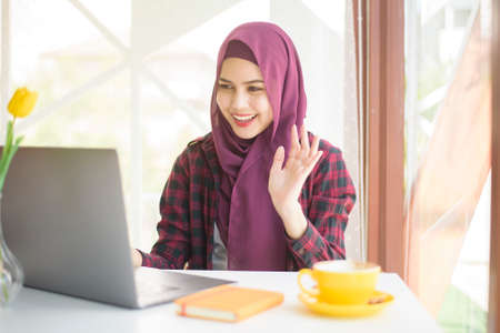 Muslim woman with hijab is working with laptop computer in coffee shop Stock Photo