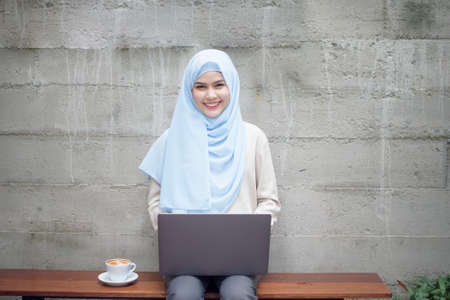 Muslim woman with hijab is working with laptop computer in coffee shop Banque d'images