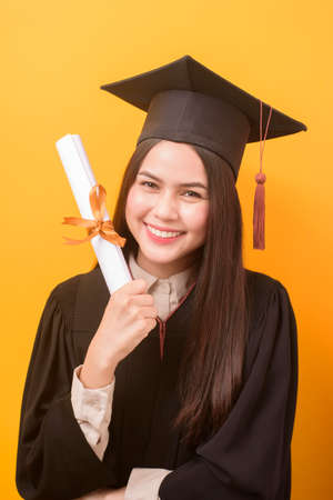 Portrait of happy Beautiful woman in graduation gown is holding education certificate on yellow background Banque d'images