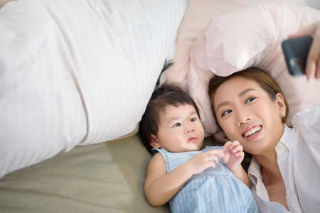 Asian Mother and her baby daughter are making selfie or video call to father in bed , Family , Home safety , parenthood , technology concept .