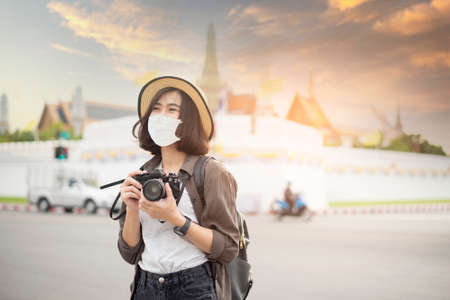 A young pretty Asian woman is wearing protective mask travelling around famous places in Bangkok city , New normal travel, covid-19 protection , safe travels , travel under COVID-19, Post- pandemic travel concept.