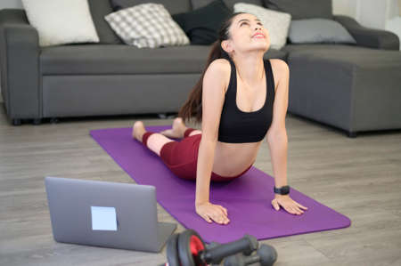 A happy young woman in sportswear is doing stretching and warming up on mat in living room at home