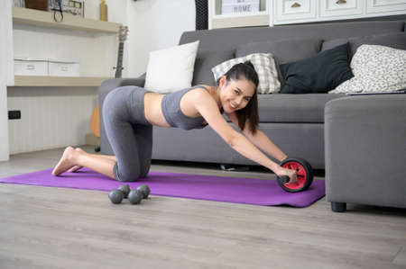 A happy young woman in sportswear is exercising with abdominal wheel at home Zdjęcie Seryjne