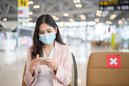 A business woman is wearing protective mask in International airport, travel under pandemic, safety travels, social distancing protocol, New normal travel concept.