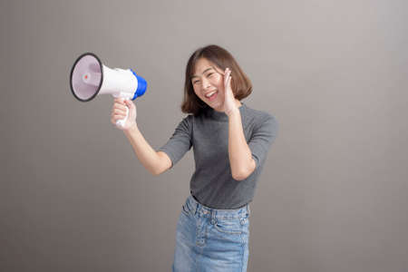 A portrait of young beautiful asian woman holding megaphone over studio background.