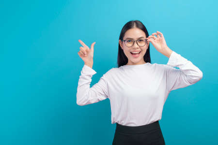 A portrait of young female wearing glasses over blue background studio, healthcare concept