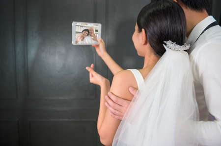 A couple in wedding gown are making video call with parents while quarantine . concept of wedding , telecommunication