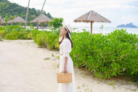 A happy beautiful woman in white dress enjoying and relaxing on the beach, Summer and holidays concept