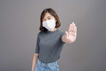 A portrait of young beautiful asian woman wearing a surgical mask over studio background Stock Photo