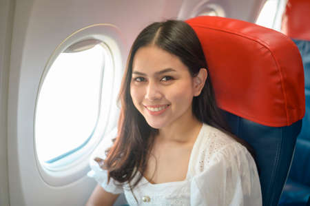 Beautiful woman traveller is using smartphone on airplane