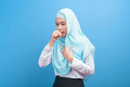 Young muslim woman with hijab  feeling sick and coughing over blue background studio. Stock Photo
