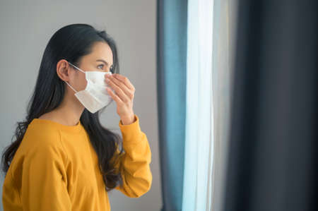 A young beautiful woman wearing a protective facial mask getting ready to go outside, Healthcare and covid-19 concept Stock Photo