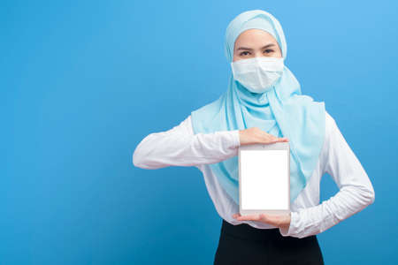 A young muslim woman with hijab wearing a surgical mask using tablet over blue background studio, covid-19 and technology concept.