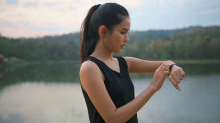 A young woman is using smartwatch while exercise in nature outdoor at sunset