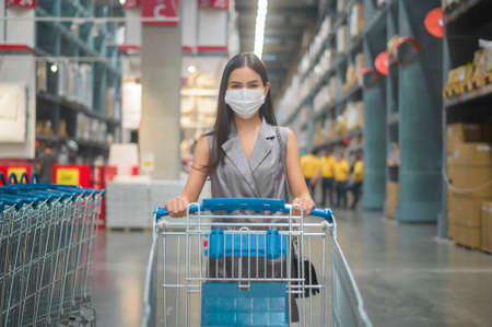 A young woman wearing a surgical mask with a trolley in shopping mall, covid-19 and pandemic concept.