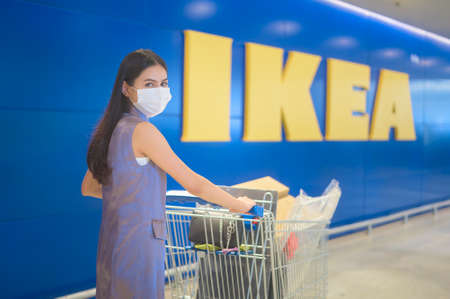 A young woman wearing a surgical mask with a shopping trolley at ikeal, covid-19 and pandemic concept.