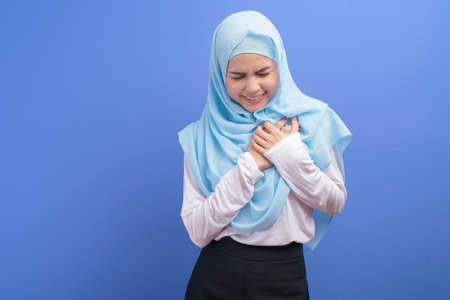 A young muslim woman wearing hijab suffering from chest pain over blue background studio, Heart attack and medical concept.