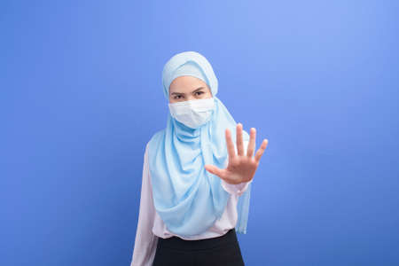 A young muslim woman with hijab wearing a surgical mask over blue background studio.