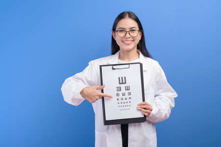 A young female ophthalmologist with glasses holding eye chart over blue background studio, healthcare concept Stock Photo