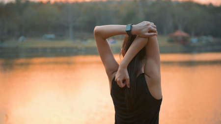 A young woman is warming up before running in nature outdoor at sunset . Stock Photo