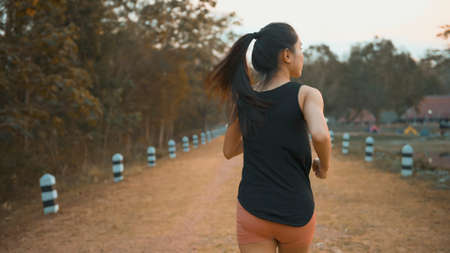 A young woman is running in nature outdoor at sunset