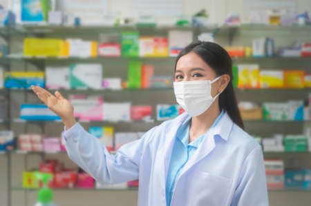 A portrait of asian woman pharmacist wearing a surgical mask in a modern pharmacy drugstore