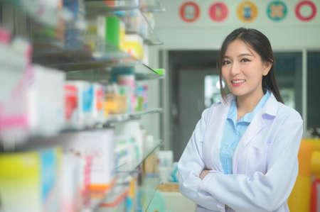 A portrait of asian woman pharmacist wearing lab coat in a modern pharmacy drugstore. Foto de archivo