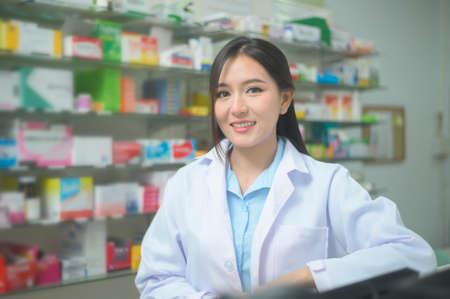 A portrait of asian woman pharmacist wearing lab coat in a modern pharmacy drugstore.