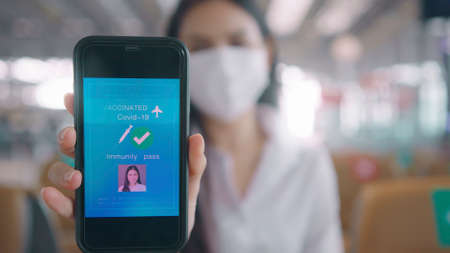 close up A business woman is wearing protective mask in International airport, showing vaccine passport on her smartphone, travel under pandemic concept