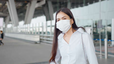 A business woman is wearing protective mask in International airport, travel under pandemic, safety travels, social distancing protocol, New normal travel concept