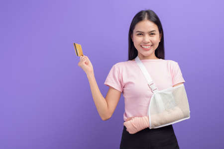 Portrait of young woman with an injured arm in a sling holding a credit card or medical insurance card over purple background in studio, insurance and healthcare concept