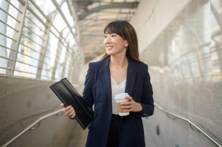 Portrait of beautiful young asian business woman is working in modern city