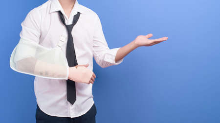 A young businessman with an injured arm in a sling over blue background in studio, insurance and healthcare concept
