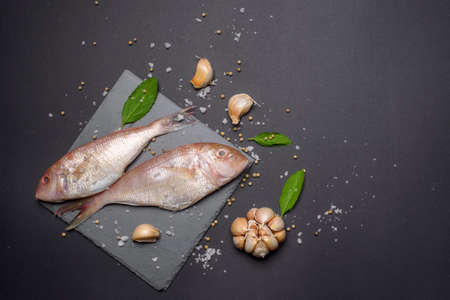 Fresh sea fish flat lay copy space on black background Stockfoto