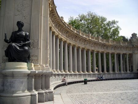 View of the Retiro Garden Lake monument with some tourists resting on the stone bench.